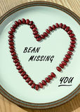 Bean Missing You A1. Red beans arranged in a heart shape with one missing placed on a white plate, text sample included Royalty Free Stock Images
