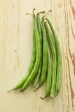 Bean pods on wooden table Stock Photography