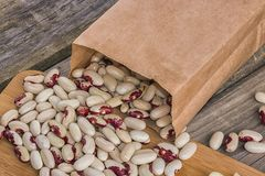Bean seeds in a paper bag. On a wooden board stock images