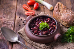 Bean soup in home crafted bowl with tomatoes on wooden table. Royalty Free Stock Image