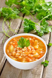 Bean soup in white bowl. On wooden table Stock Photos