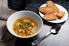 Bean soup in white plate with metal spoon, several toast on whit Stock Photo