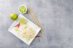 Bean sprouts in white plate. Fresh bean sprouts on white square plate and chopsticks. Concept of healthy foods, vegetarian food. Top view Stock Images