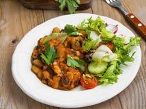Bean stew with fresh parsley, salad, cucumber, radish and tomato Stock Photo