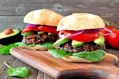 Bean and sweet potato veggie burgers over a wood background. Bean and sweet potato veggie burgers with avocado and spinach against a rustic wooden background Stock Photos