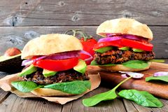 Bean and sweet potato veggie burgers over a wood background. Two vegetarian bean and sweet potato burgers with avocado and spinach against a rustic wooden Stock Photos