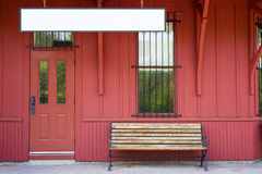 Beanch by blank sign - red station. Empty bench by blank sign against red wooden walls Royalty Free Stock Photos