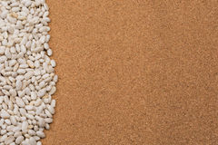 Beans bordering on side background. Beans border the side of a neutral colored cork background Royalty Free Stock Photo