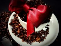 Beans brown aroma black cup ceramic bow. Redbow coffee cafe caffeine aroma black Royalty Free Stock Photo