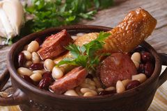 Beans with chicken legs and grilled sausages close up horizontal Stock Photos
