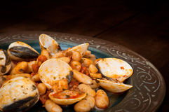 Beans and chorizo with clams. Beans and chorizo with fresh clams. Delicious Spanish seafood dish served on a rustic plate Royalty Free Stock Image
