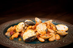 Beans, clams and chorizo. Beans and chorizo with fresh clams. Delicious Spanish seafood dish served on a rustic plate Royalty Free Stock Photos