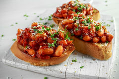 Beans fried in tomato sauce on toasted bread with cross salad sprinkle Stock Photography