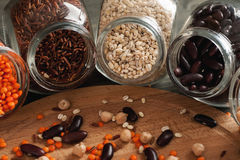 Beans and grain mix in glass jars on a wooden table. Closeup shot, selective focus royalty free stock images