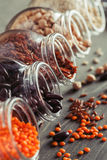 Beans and grain mix in open glass jars on a gray wooden table. Selective focus, closeup, vertical royalty free stock image
