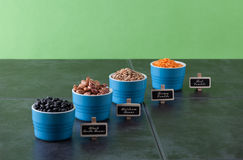 Beans and grains varieties. Red and brown lentils, heirloom beans, and black turtle beans on dark grungy surface. with labels. Perspective view horizontal image Royalty Free Stock Images