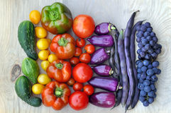 Beans, grapes, tomatoes, peppers, cucumber on light wooden surface. Autumn food background. Beans, grapes, tomatoes, peppers, cucumber on light wooden surface Stock Image