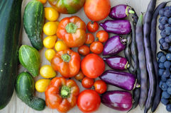 Beans, grapes, tomatoes, peppers, zucchini, cucumber on light wooden surface. Royalty Free Stock Photography