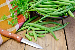 Beans green on board with knife and napkin Stock Images