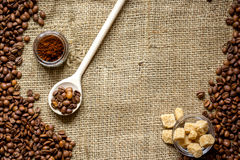 Beans, ground coffee and sugar cane on linen cloth Royalty Free Stock Images