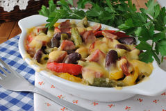 Beans with ham and vegetables, baked with cheese Stock Image