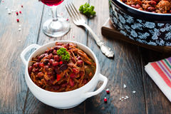 Beans with pork stewed in spicy tomato sauce with onion, paprika, beer, bell and pink pepper. Royalty Free Stock Image