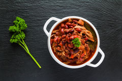 Beans with pork stewed in spicy tomato sauce with onion, paprika, beer, bell and pink pepper. Royalty Free Stock Images