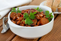 Beans with sausages in sauce with parsley Royalty Free Stock Photography
