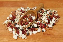 Beans with a scoop. Mix if dried beans with a scoop on a wooden chopping board Royalty Free Stock Photography