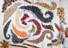 Beans, seeds and herbs forming swirls royalty free stock photography