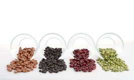 Beans and split peas spilling out of glass jars Royalty Free Stock Image