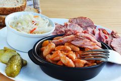 Beans stew in tomato sauce with smoked ham hock meat pickles and coleslaw Stock Image