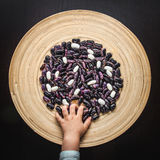 Beans and thief. Two kinds of beans in the wooden plate and little hand Royalty Free Stock Images