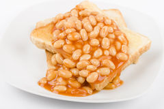 Beans on Toast. Slices of toasted white bread, buttered and topped with baked beans. Simple British breakfast meal royalty free stock images