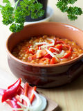 Beans in tomato sauce in a brown bowl. White beans in tomato sauce with red peppers and onion Royalty Free Stock Images