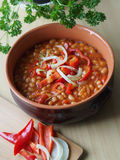 Beans in tomato sauce in a ceramic bowl. White beans in tomato sauce with red peppers and onion Stock Photography