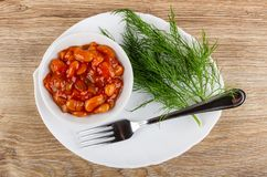 Beans with vegetables and tomato sauce in bowl, dill, fork on dish on wooden table. Top view. Beans with vegetables and tomato sauce in white bowl, fresh dill royalty free stock photography