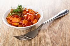 Beans with vegetables and tomato sauce, dill in bowl, fork on table. Beans with vegetables and tomato sauce, dill in white bowl, fork on wooden table royalty free stock images