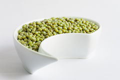 Beans in white ceramics bowl. Green small beans in white ceramics bowl on white background Royalty Free Stock Photography