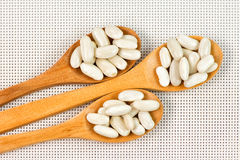 Beans in wooden spoons Royalty Free Stock Images