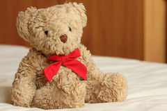 Bear On The Bed. A teddy bear with a red bow sitting on a bed royalty free stock photo