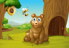 A bear and a bee near a treehouse Royalty Free Stock Photos
