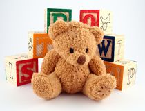 Bear and Blocks. A teddy bear in front of a stack of wooden blocks royalty free stock image