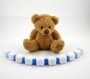 Bear and Blue Beads. A teddy bear and a string of beads Royalty Free Stock Images