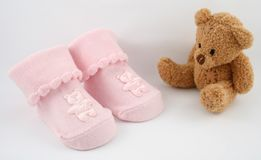 Bear and Booties. A pain of pink baby booties and a plush bear stock image