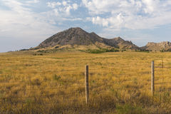 Bear Butte. A scenic butte with foreground grass and fence royalty free stock image