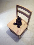 Bear in chair under spotlight Royalty Free Stock Image