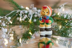Bear with Christmas presents. Christmas decoration: bear with presents, pearl lights and a branch of Christmas tree with reflection Royalty Free Stock Image