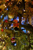 The bear in the (Christmas) tree. A close-up of of a figurine of a teddy bear in a Christmas tree with baubles, lights and other ornaments in the background stock image