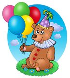 Bear clown with balloons on meadow Stock Image